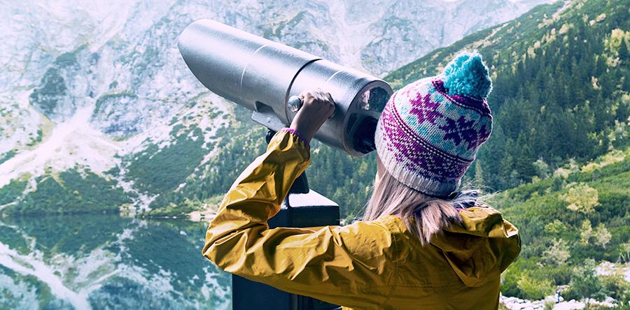 Junge Frau schaut durch ein Fernglas auf die Berge, Fokus on